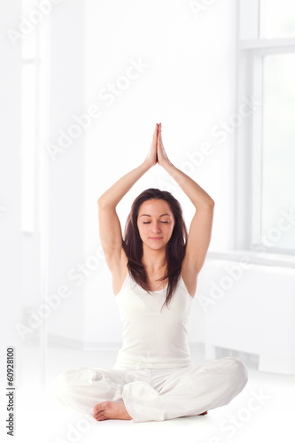 Fit young woman performing some yoga style exercise.Studio shot,