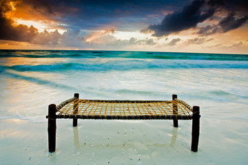 Bed on a sandy beach touching the sea under dramatic sky