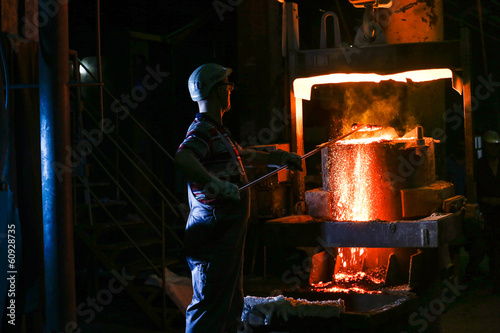 A founder holding a crucible of molten cast iron