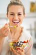 Smiling young woman eating fresh fruit salad