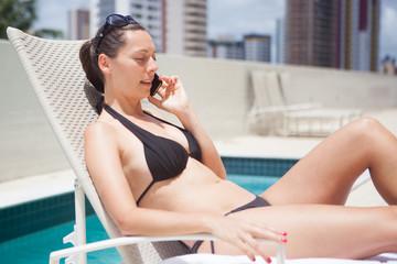 Frau telefoniert am Pool