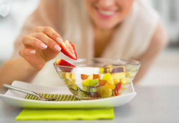 Closeup on happy woman serving fresh fruit salad