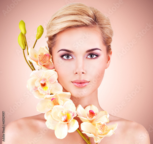Woman with health skin and flowers at face.
