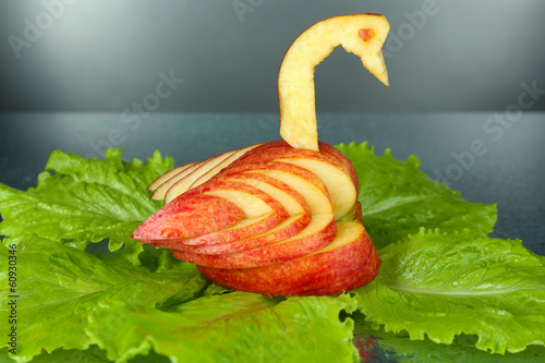 Carving fruit pattern of swan on grey wet background