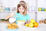 Beautiful little girl eating breakfast in kitchen at home