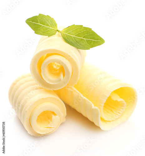 Curls of fresh butter with basil, isolated on white