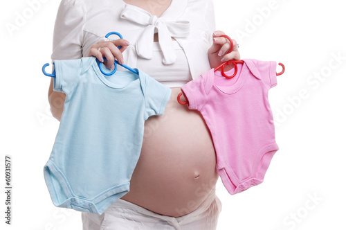 Pregnant woman holding bodysuit for a baby girl and boy