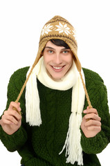 Man dressed for a cold winter with hat and scarf smiling.