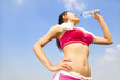 young woman drinking water after running session