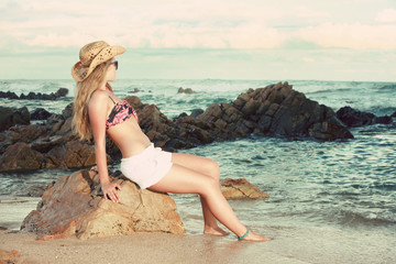 Attractive blonde with hat and sunglasses looking away
