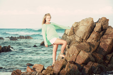Blonde lady standing on rocks in the ocean