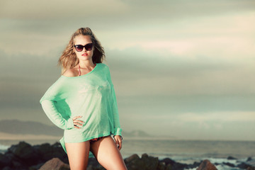 Blonde lady with green jersey standing on the beach