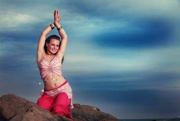 Teen Belly dancer performing on the rocks