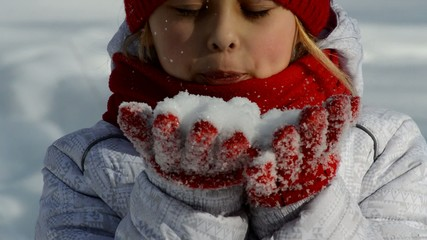 girl blows snow from hands