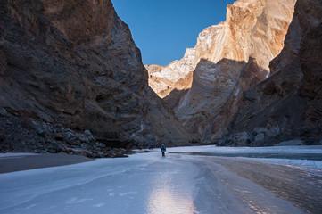 Trekker walking on the frozen Zanskar River in Ladakh.