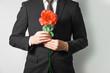 赤いバラを持ったスーツの男性