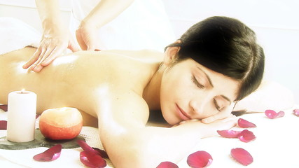 Woman surrounded by roses and candles getting massage