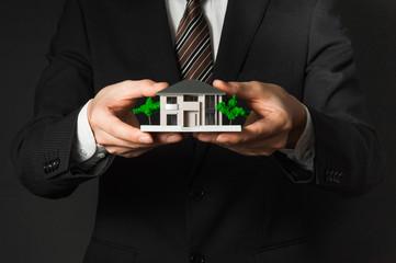 スーツを着た男性と家の模型