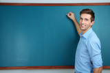 Young teacher near chalkboard in school classroom