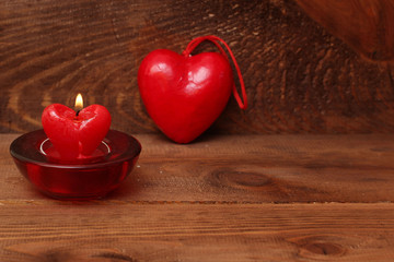 burning candle heart  on wooden background