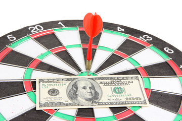 Dart on dartboard and money close up. Concept of success.