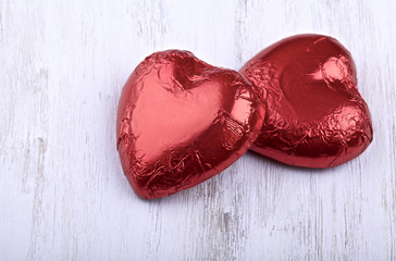 Chocolate hearts candies on a painted white background