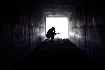 sad man sitting in the tunnel