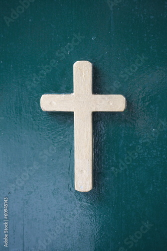 bronze cross on green background