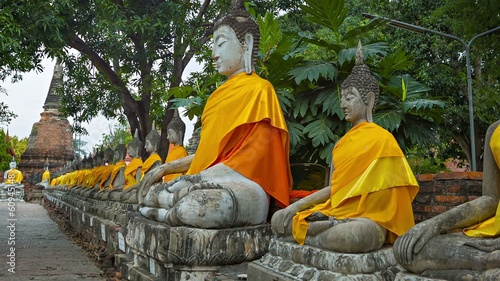 Row of Buddha statues in orange clothes