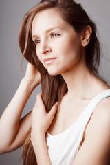 Jeune femme brune lissant ses cheveux