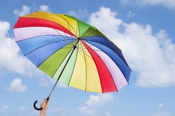 Rainbow umbrella in woman hands against cloudy sky