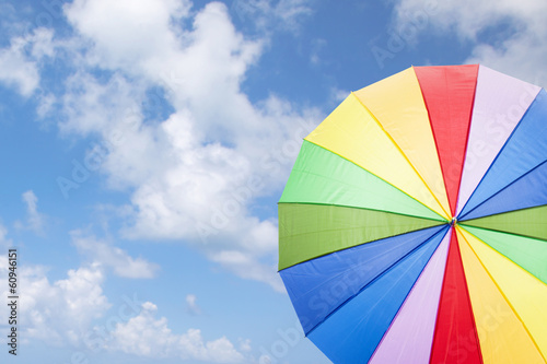 Rainbow umbrella against cloudy sky