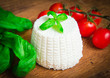 Fresh ricotta with basil and cherry tomatoes on wooden table