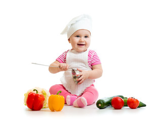Baby dressed in cook hat with healthy food vegetables