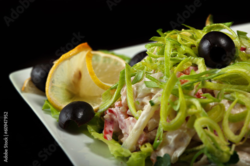 Delicious salad garnished leek, lemon and olives