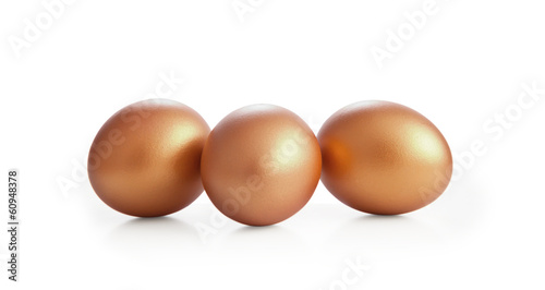 Golden eggs on white background.