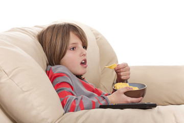 boy eating chips and watching television
