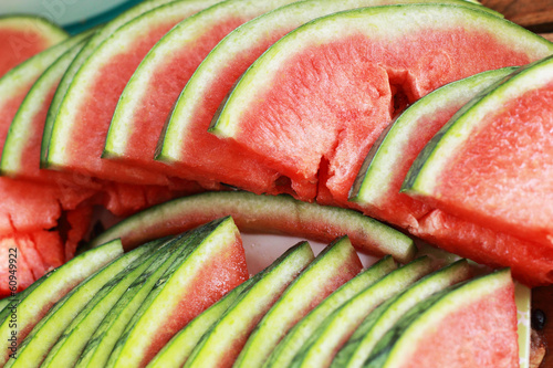 Watermelon fruit sliced ​​into pieces on the wooden floor.