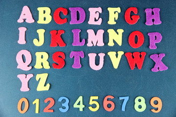 English alphabet and numbers on school desk background