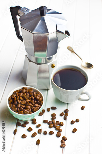 coffee maker with cup of coffee and coffee beans