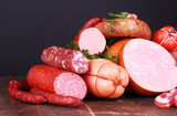 Lot of different sausages on wooden table on black background
