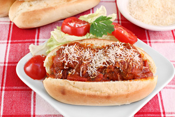 Meatball parmesan sub sandwich with side salad.
