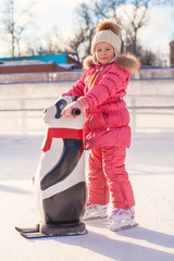 Little happy girl learning to skate on the rink