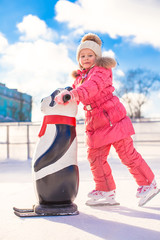 Little happy girl skating on the ice-rink