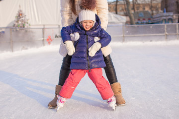 Little adorable girl with her mom learning to skate