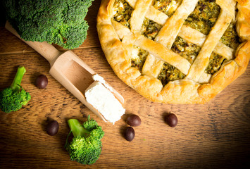 Broccoli pie with ricotta and olives on wooden table