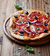 Pizza with salami, tomatoes and red onion