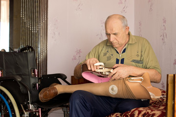 Pensioner fitting his artificial leg