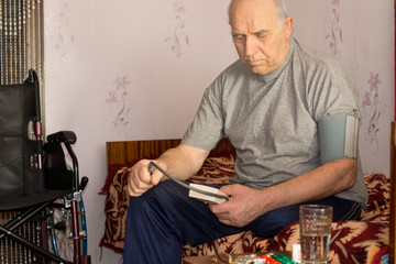 Senior disabled man taking his own blood pressure