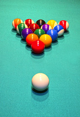 Billiard balls in the position of the pyramid on green baize